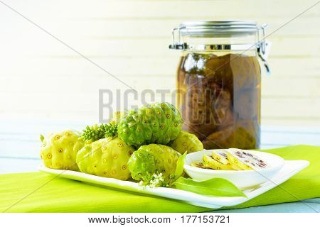 Noni fruit in the dish and noni slice with noni fermented on green checkered fabric
