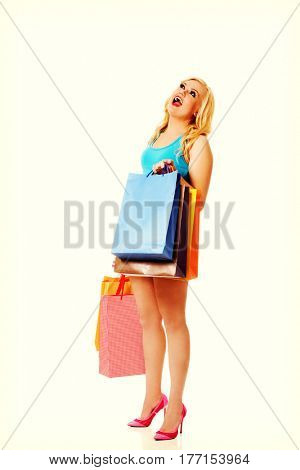 Shocked young woman holding shopping bags