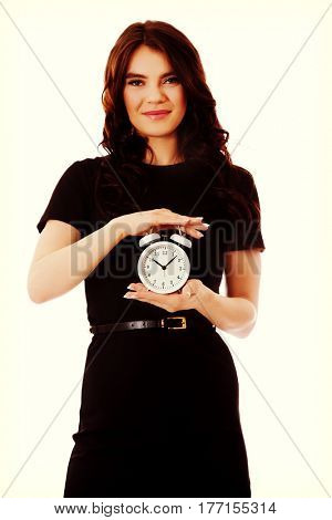 Happy young businesswoman holding alarm clock