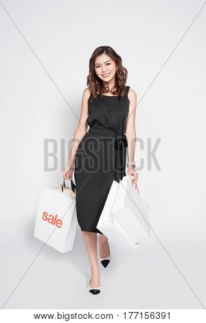Beautiful Asian Woman Wearing Black Dress With Shopping Bag Standing Over White.