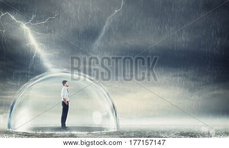 Businessman safely inside a sphere during a storm . Protection from the crisis concept