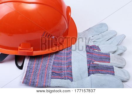 Orange hard hat, safety glasses, gloves and measuring tape on white isolated.