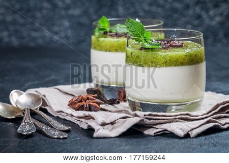 Fruit dessert green panna cotta with mint in a glass over black background