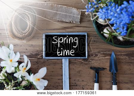 Sign With English Text Springtime. Sunny Spring Flowers Like Grape Hyacinth And Crocus. Gardening Tools Like Rake And Shovel. Hemp Fabric Ribbon. Aged Wooden Background