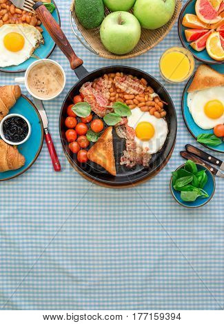 Healthy breakfast table - fried egg beans tomatoes bacon toast various fruits juice and coffee on a rustic table with copy space top view