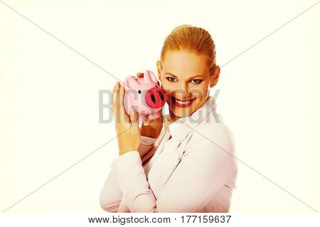Young business woman holding piggybank