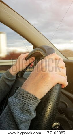 Female hands on car steering wheel driving vehicle on two lane highway