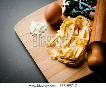 italian tagliatelle displayed on a chopping board together with some ingredients