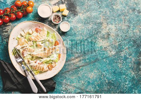 Delicious caesar salad with croutons, grilled chicken breast, grated parmesan cheese and cos lettuce, with sauce in the gravy boat, simply and healthy recipe, top view