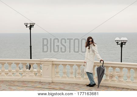 Young woman (brunette) in a white coat walks along the promenade. Selective focus.