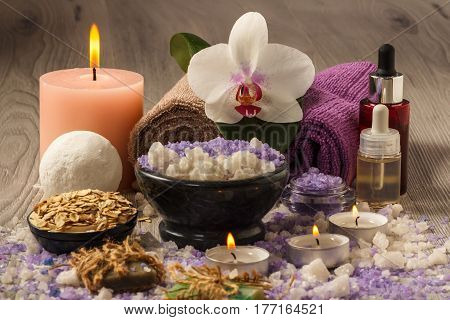 Spa products with orchid flower bowl with sea salt bottles with aromatic oil soap scrub candles and towels on wooden board