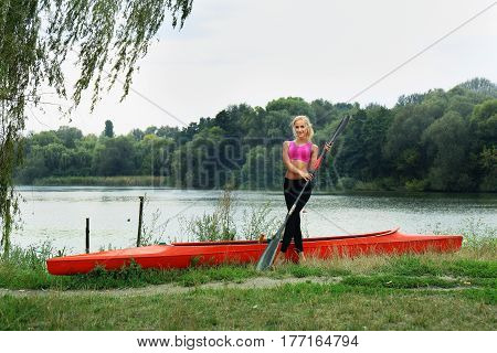 Girl with paddle near the kayaks on the river bank