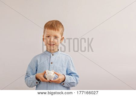 Cute little boy holding a piggy bank or money box. Concept child and money.