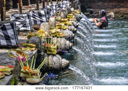 BALI, INDONESIA - SEPTEMBER 27, 2012: Balinese woman taking purifying bath in the Tirta Empul Temple in Bali Indonesia