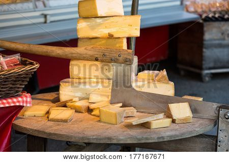Cheese for sale and an old cutter or chopper used for slicing cheeses in a market at Salzburg Austria
