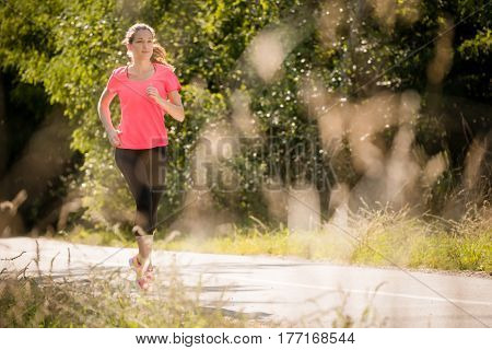 Young woman jogging in park on summer sunny day
