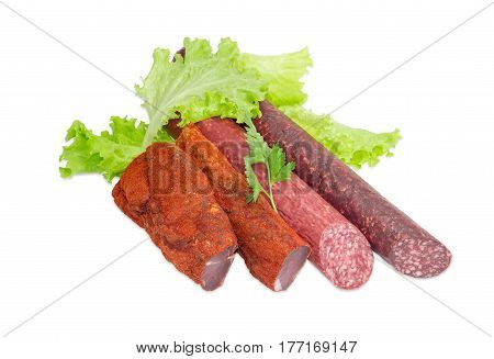 Partly sliced two pieces of the dried pork tenderloin cooked smoked sausage and dry sausage with parsley twig on the lettuce on a light background