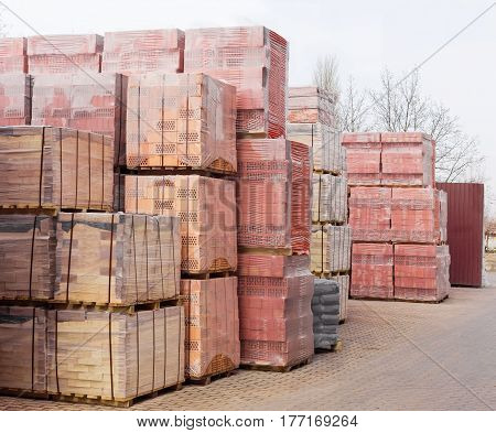 Packed yellow and red perforated bricks with round and rectangular holes on the wooden pallets on a warehouse