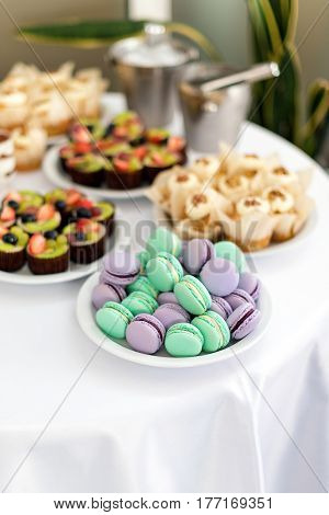 Turquoise and violet macarons. Wedding cakes on the table. Sweet desserts. Selective focus.