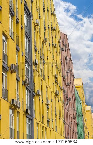 Fragment of a multicolored facade of the modern multi-story apartment complex with the outside parts of a split-type air conditioners against the background of the sky with clouds