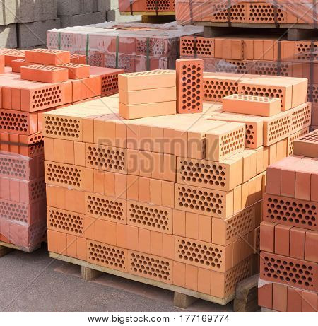 Perforated bricks of yellow and red colors with round holes on a several wooden pallets on a warehouse