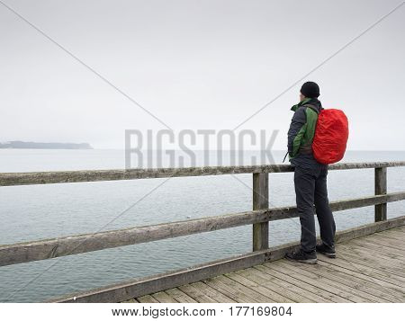 Man In Autumn Mist On Pier Above Sea. Depression, Dark  Atmosphere. Mole, Wet Board Above Sea.