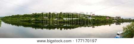 View from the banks of the Dniester River in Mogilev-Podolsky Ukraine on Moldovan houses on the opposite bank of the river horizontal photo