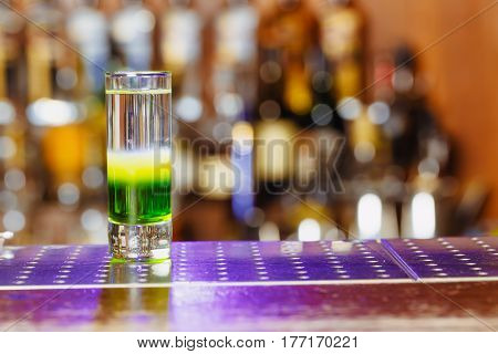 Cocktail shot green mexican with banana liqueur lemon juice and tequila. Horizontal photo