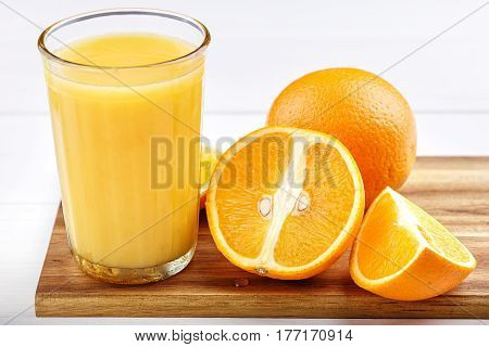 Fresh from oranges in a glass on wooden cutting board. Next to them are cut oranges. Horizontal photo