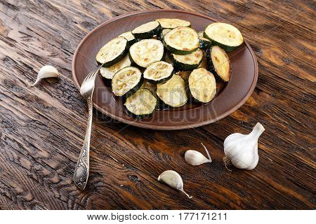 Fried zucchini in a clay plate on a wooden table. burlap on the table garlic fork