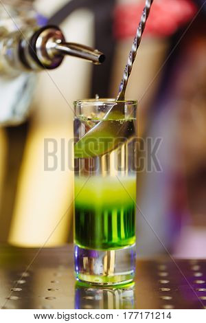 Cocktail shot green mexican with banana liqueur lemon juice and tequila. Vertical photo