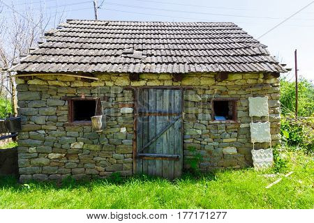 Old stone house with a tiled roof around the house growing dense green grass horizontal photo