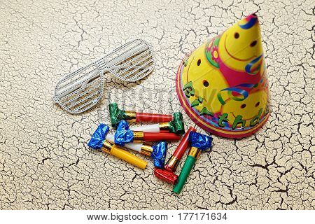 whistles toy cap and glasses on a child's birthday on a white background craquelure top view