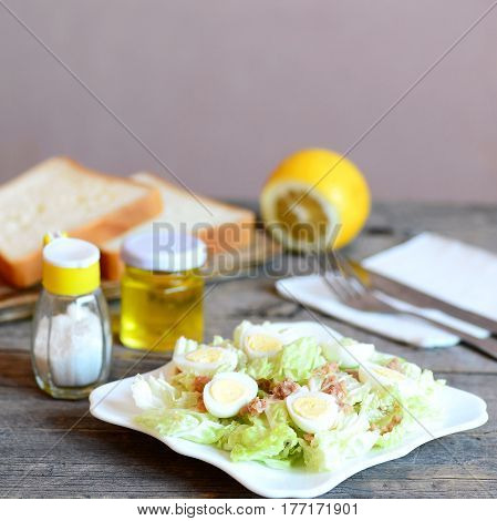 Homemade salad with napa cabbage, quail eggs and canned tuna fish. Healthy salad on a plate, fork, knife, olive oil bottle, salt shaker, bread slices on old wooden table. Easy starter food. Closeup
