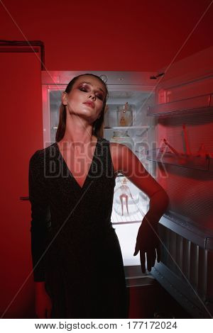 Vertical image of woman in dress with closed eyes which standing near the fridge. Conceptual photo