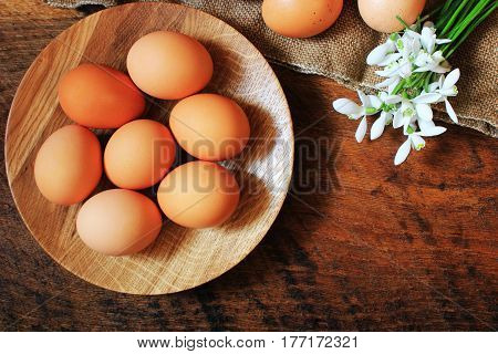 Easter background. Rustic wooden table with plate, egg, flowers and cutting board . Top view. Copy space.