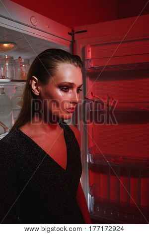 Side view of mystery woman in dress which standing near the fridge. Vertical image. Conceptual picture