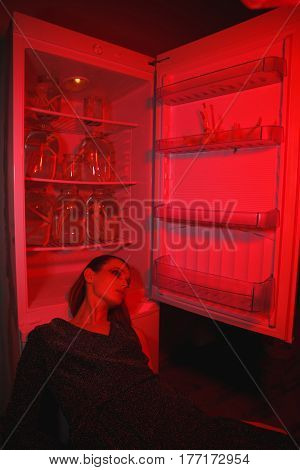 Vertical image of young woman in dress which lying near the fridge. Conceptual photo