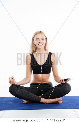 Image of cheerful fitness woman sitting make yoga exercises and posing isolated over white background. Listening music with earphones with eyes closed.