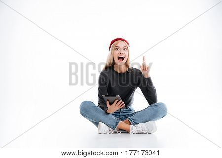 Happy Female Hipster with open mouth which sitting with tablet computer and showing forefinger over white background