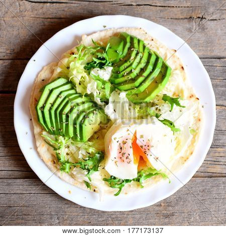 Poached egg, fresh avocado slices, salad, chinese cabbage, dried herbs, sauce on a tortilla. Tasty tortilla with filling on a plate isolated on old wooden background. Vegetarian meal. Top view