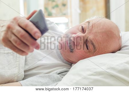 An elderly man turns off the alarm on the phone in the morning or checks the calls. Morning of the day off