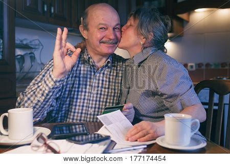 A Married Couple Counts Money And A Budget. The Wife Kisses Her Husband's Cheek. He Shows The Sign O