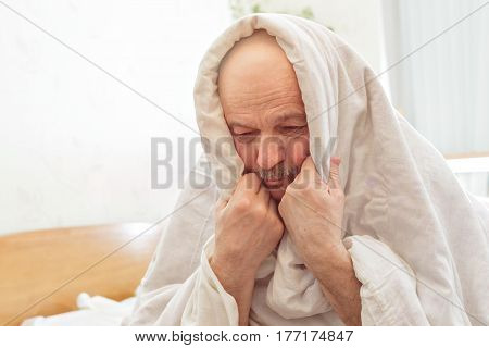 Sad Elderly Man Suffers From Insomnia. He Covered Himself With A Blanket To Make It Easier To Fall A
