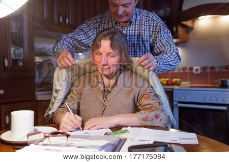 An elderly man hides his wife with a scarf. She sits at the table and makes calculations of the family budget.