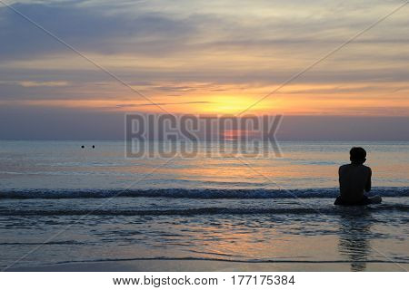 Travel to island Koh Chang, Thailand. The sitting man on the beach on the colorful sunset.