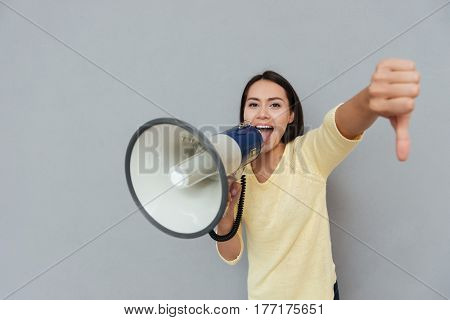 Woman in sweater which screaming in megaphone and showing thumb down while looking at camera. Isolated gray background