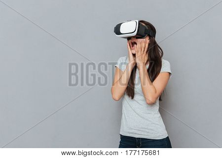 Surprised woman using virtual reality device in studio and holding her cheeks over gray background