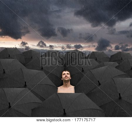 young man standing alone in the rain without an umbrella