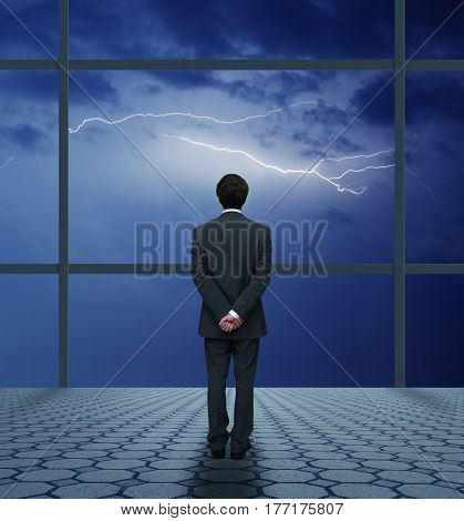 businessman in a suit watching the storm from his office